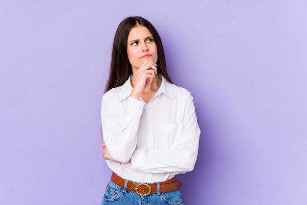 Giovane donna caucasica sul muro viola guardando lateralmente con espressione dubbiosa e scettica.