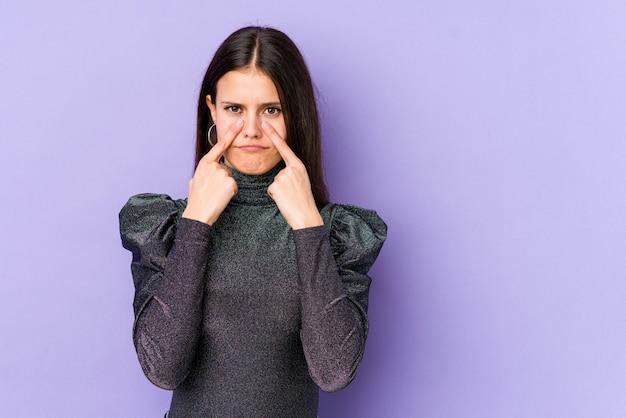 Giovane donna caucasica sul muro viola piangendo, insoddisfatto di qualcosa