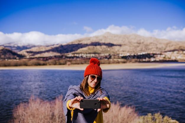 Giovane donna caucasica sulla montagna nel giorno soleggiato facendo uso del telefono cellulare.