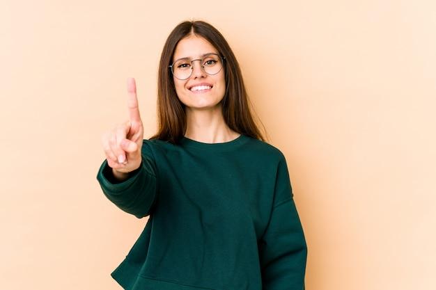 Giovane donna caucasica sulla parete beige che mostra numero uno con il dito.