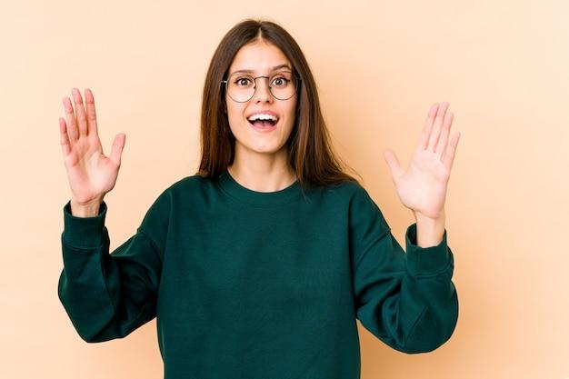 Giovane donna caucasica sulla parete beige che riceve una piacevole sorpresa, eccitata e alzando le mani.