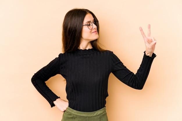 Giovane donna caucasica sulla parete beige gioiosa e spensierata mostrando un simbolo di pace con le dita.