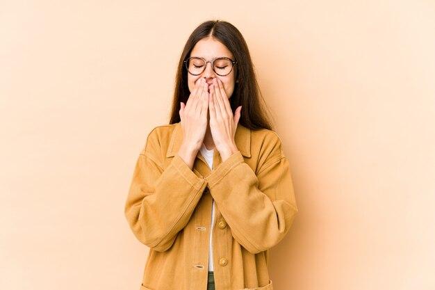 Giovane donna caucasica sulla parete beige ridendo di qualcosa, coprendo la bocca con le mani.