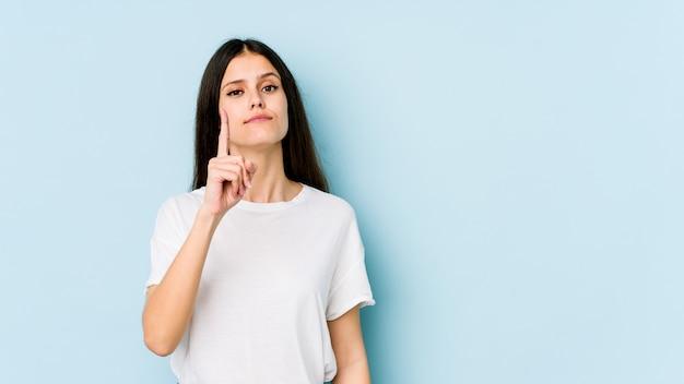 Giovane donna caucasica sulla parete blu che mostra il numero uno con il dito.