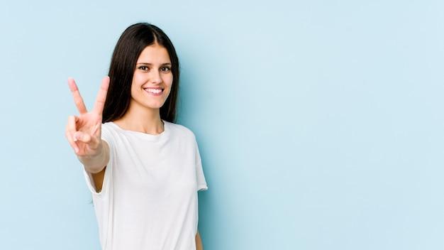 Giovane donna caucasica sulla parete blu che mostra il segno di vittoria e che sorride ampiamente.