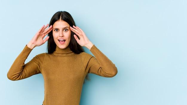 Giovane donna caucasica sulla parete blu che riceve una piacevole sorpresa, eccitata e alzando le mani.