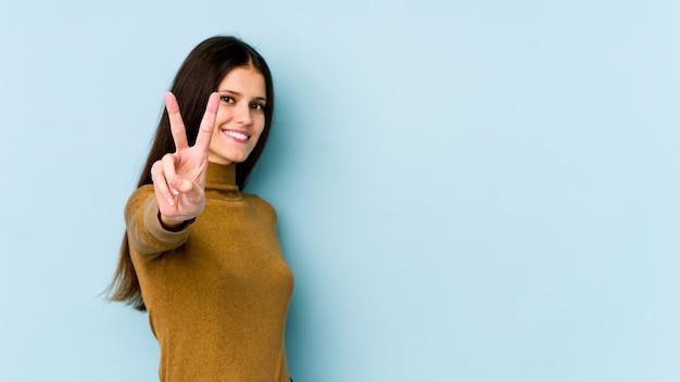 Giovane donna caucasica sulla parete blu gioiosa e spensierata mostrando un simbolo di pace con le dita.