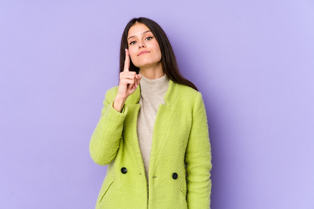 Giovane donna caucasica sulla parete viola che mostra numero uno con il dito.