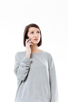 Giovane donna caucasica triste che parla dal telefono.