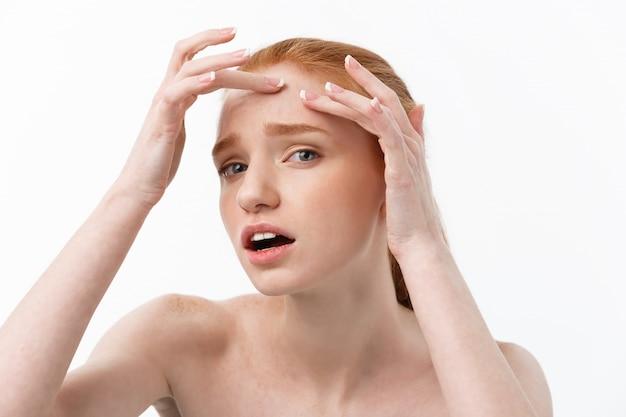 Giovane donna caucsiana stringe l'acne sul volto della bellezza