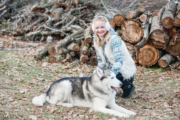 Giovane donna che abbraccia il suo cane husky