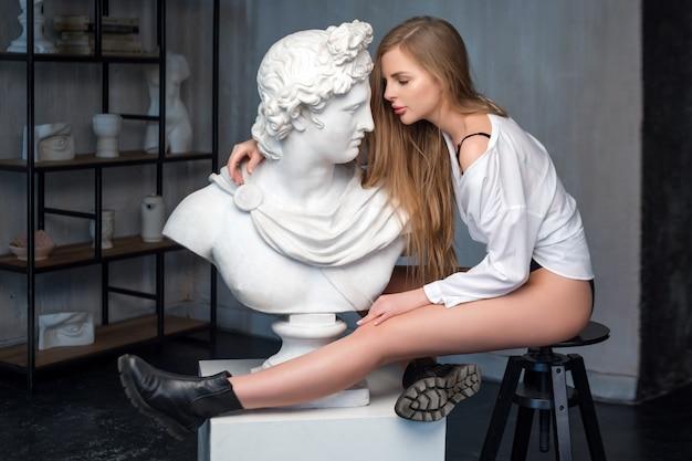 Giovane donna che abbraccia la scultura del busto di dio apollo. antico dio greco del sole e della poesia intonaco copia di una statua in marmo su sfondo muro di cemento grange. arte antica e bellezza vivente