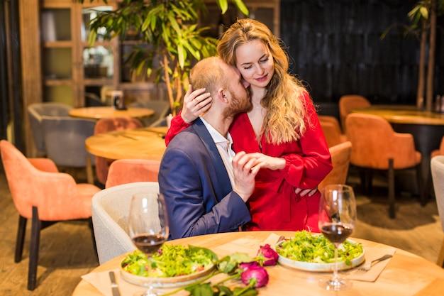 Giovane donna che abbraccia uomo al tavolo