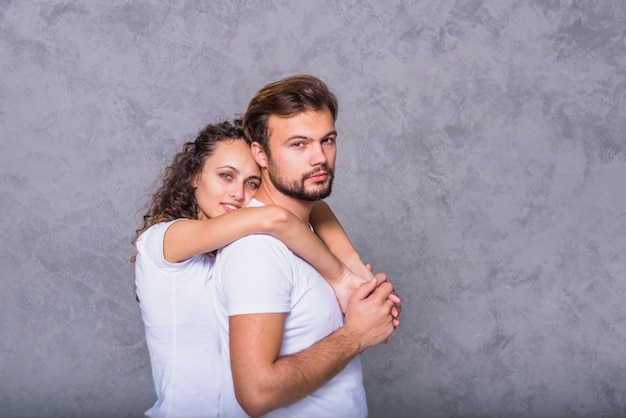 Giovane donna che abbraccia uomo da dietro