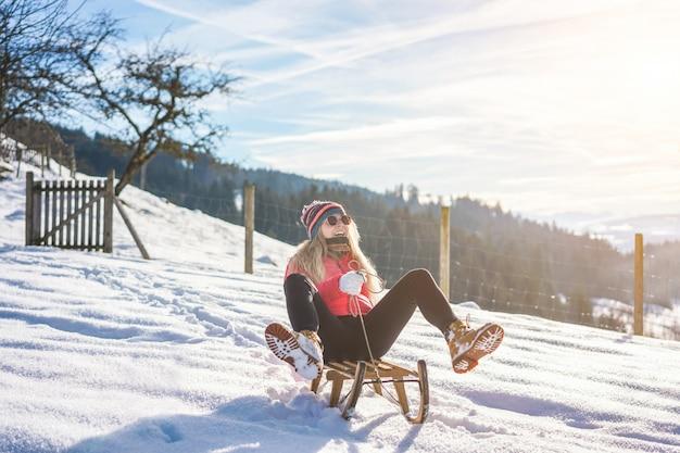 Giovane donna che accelera con lo sledding d'annata sull'alta montagna della neve