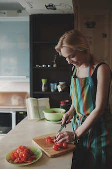 Giovane donna che affetta i pomodori