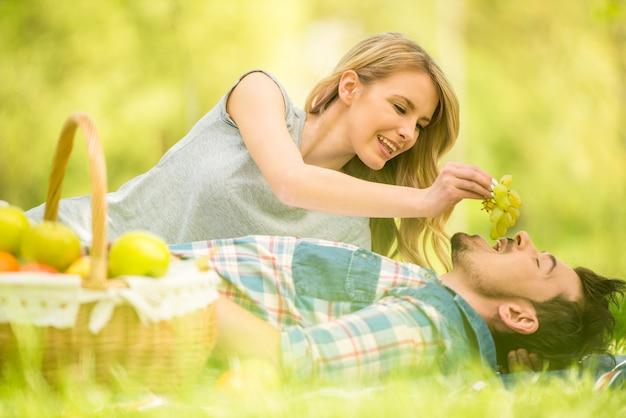 Giovane donna che alimenta il suo uomo con l'uva.