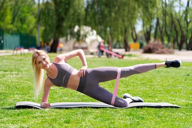 Giovane donna che allunga facendo l'oscillazione della gamba all'aperto