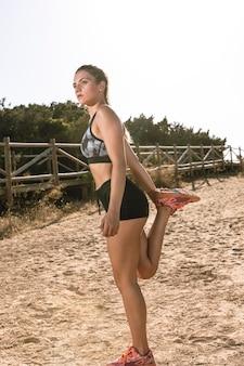 Giovane donna che allunga il suo ritardo sulla sabbia