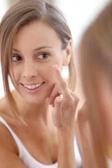 Giovane donna che applica la crema anti-rughe