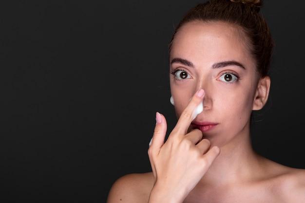 Giovane donna che applica la crema per il naso
