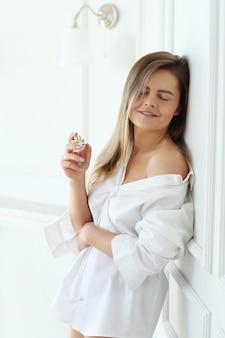 Giovane donna che applica profumo.