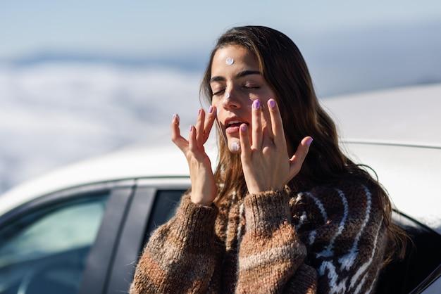 Giovane donna che applica protezione solare sul suo fronte nel paesaggio della neve