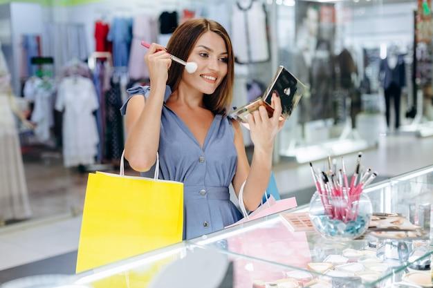 Giovane donna che applica trucco alla boutique di moda