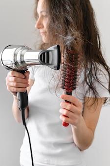 Giovane donna che asciuga i capelli