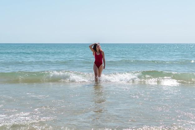 Giovane donna che attraversa il mare e si diverte