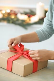 Giovane donna che avvolge i regali di natale