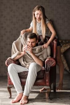 Giovane donna che avvolge il suo ragazzo con lo scialle che si siede sulla poltrona bere caffè