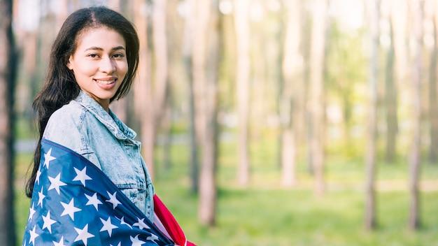 Giovane donna che avvolge in bandiera americana in natura