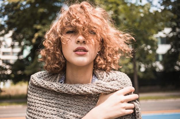 Giovane donna che avvolge in sciarpa nel parco