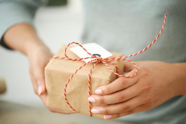 Giovane donna che avvolge regalo di natale