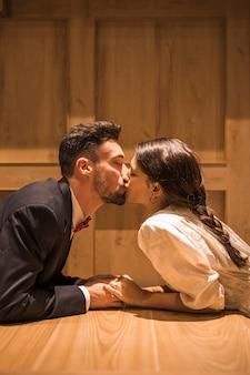 Giovane donna che bacia uomo disteso sul pavimento