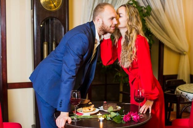 Giovane donna che bacia uomo sulla guancia sopra il tavolo