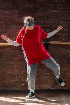 Giovane donna che balla davanti al muro di mattoni