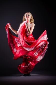 Giovane donna che balla in abito rosso