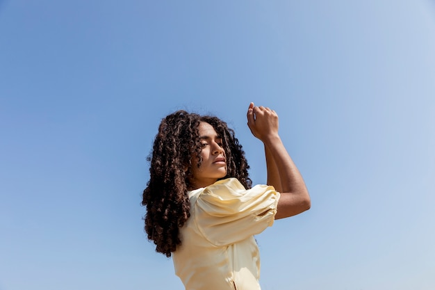 Giovane donna che balla sul fondo del cielo