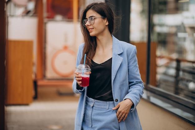 Giovane donna che beve bevanda ghiacciata fuori strada