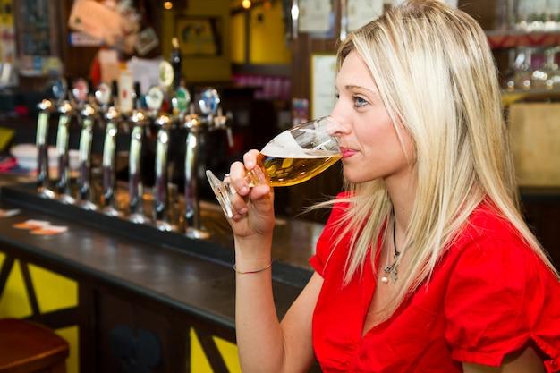 Giovane donna che beve birra in un pub