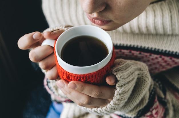 Giovane donna che beve caffè caldo