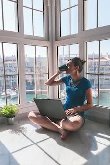 Giovane donna che beve caffè, lavorando con il computer portatile alla finestra di casa sul porto turistico. f