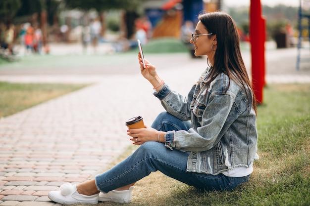Giovane donna che beve caffè nel parco