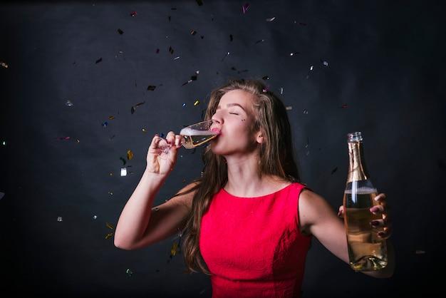 Giovane donna che beve champagne