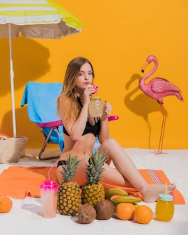 Giovane donna che beve cocktail sulla spiaggia