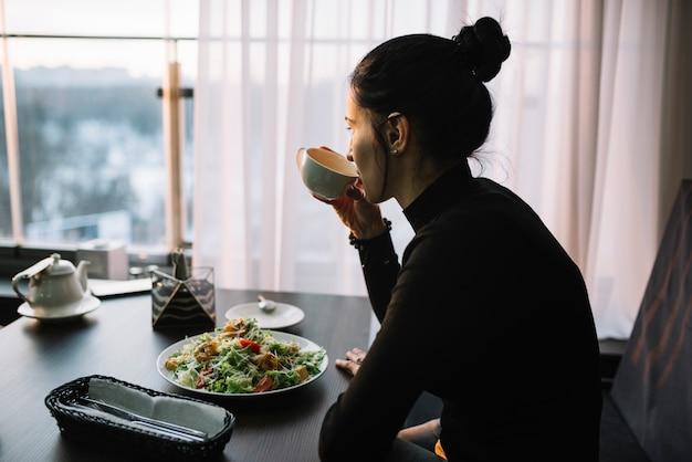 Giovane donna che beve dalla tazza al tavolo con insalata vicino alla finestra