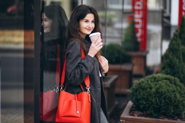 Giovane donna che beve il caffè in città