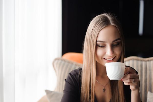 Giovane donna che beve il caffè in un bar e utilizzando un telefono cellulare